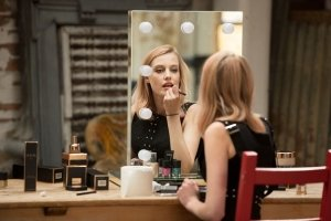a model applying make-up in a mirror we provided for TV product placement